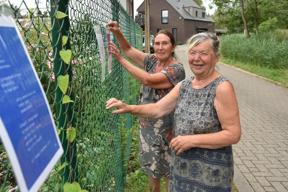 Monique De Ryck (rechts) en Godelief Cuyckens bij enkele gedichten aan de draad.