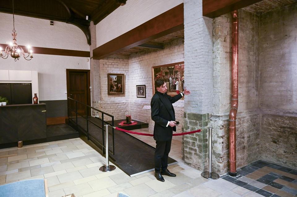 Sinds de renovatie van het bijgebouw ligt onder andere de zijmuur van de Sint-Andrieskerk bloot. Dat laat pastoor Rudi Mannaerts zien.