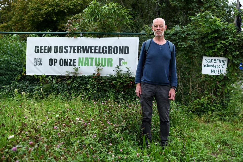 Frank Van Houtte aan het omheind voormalig asbeststort van Eternit bij twee protestborden van de actiegroep Red onze Kleiputten. Het stort wordt nu wel gesaneerd, maar met Oosterweelgrond, véél Oosterweelgrond.
