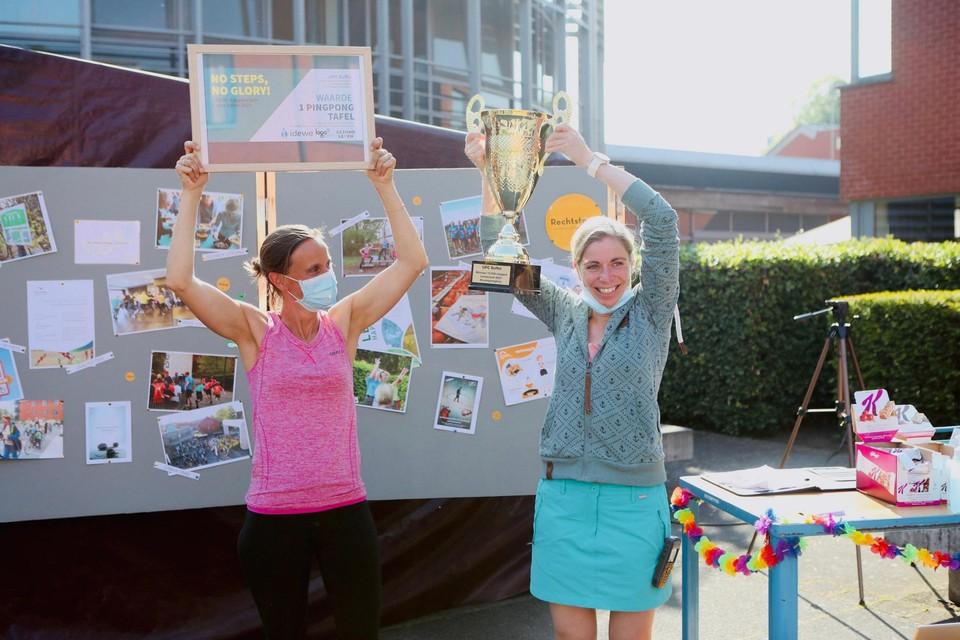 Medewerkers Liesbeth Buytaert en Sofie Dauwen, psychomotore therapeuten, tonen hoe blij ze zijn met de trofee.