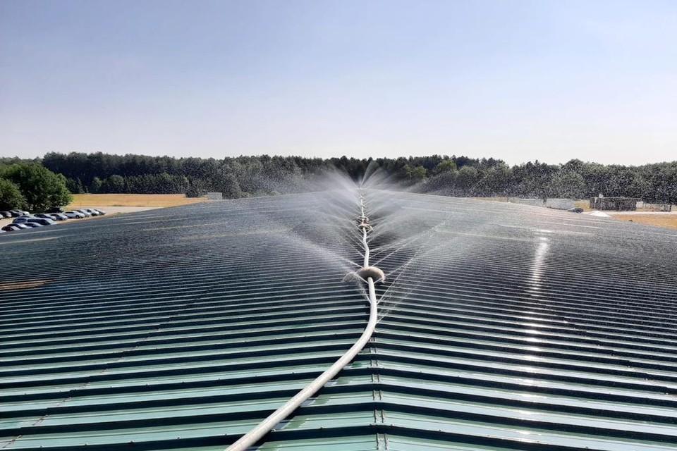 De installatie sproeit koud water op het dak van de loods.