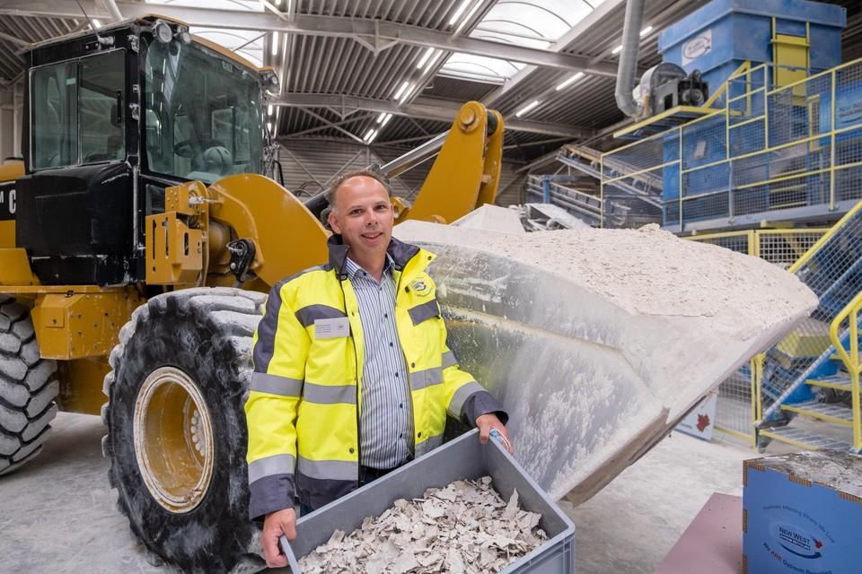 General manager Maarten Hendriks met op de achtergrond de gepatenteerde machine die gipsafval verpulvert. Het papier van de verwerkte gipsplaten wordt ook in de bouw hergebruikt.