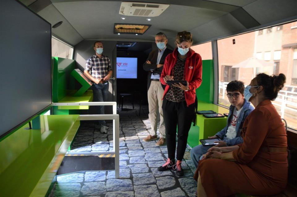 Esila doet de verkeersquiz met een tablet binnen in de Mobibus.