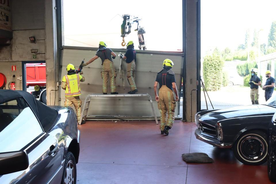 De brandweer moest de volledig beschadigde poort van de garage komen weghalen.