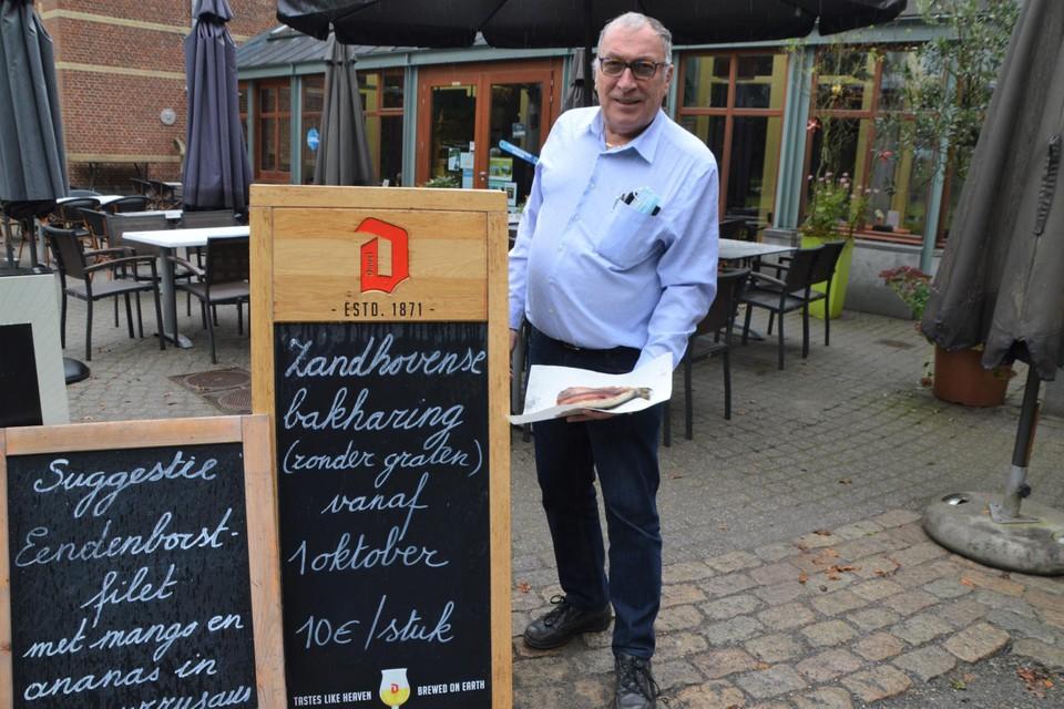 Jef Vertruyen met in zijn hand een Zandhovense bakharing op boterpapier voor het bord aan De Remise in het Vrieselhof in Oelegem.