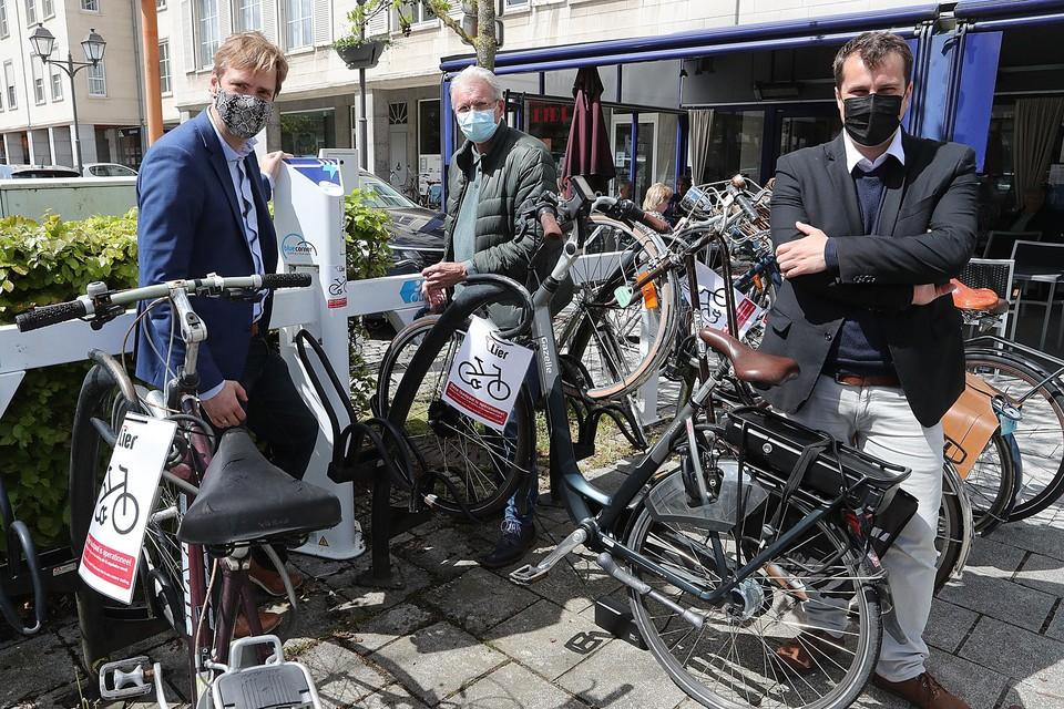 Schepen Rik Pets laadt zijn fiets op. Schepenen Bert Wollants en Rik Verwaest houden een oogje in het zeil.