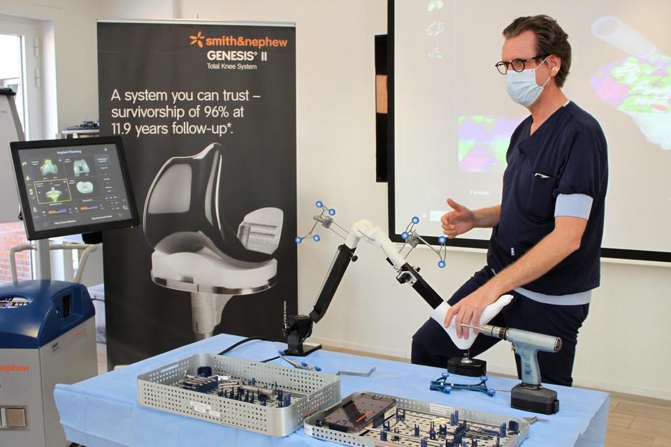 Dokter Frank Verheyden demonstreert de robot die helpt bij het plaatsen van een knieprothese.