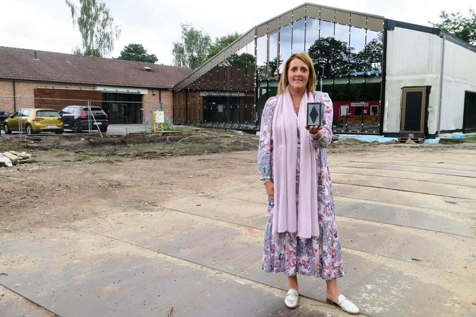 Valérie Jonkers, coo van Care Property Invest, op de werf voor de aanbouw van de historische tiendenschuur (links) in een bewust contrasterende hedendaagse architectuur. De gevel is bijna volledig uit glas opgetrokken..