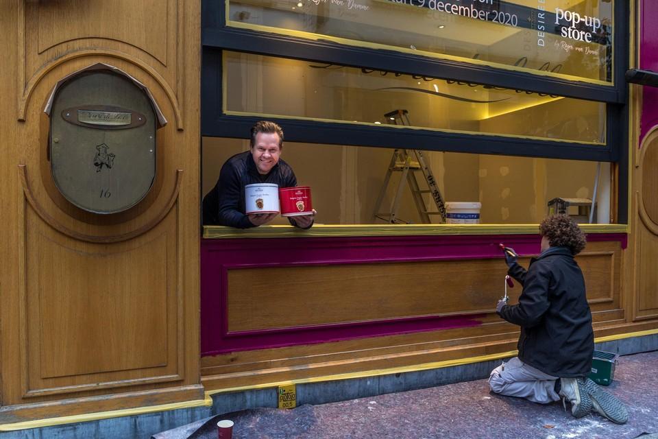 Een schilder doet zijn werk, terwijl Roger van Damme zijn koekjesdozen aanprijst.