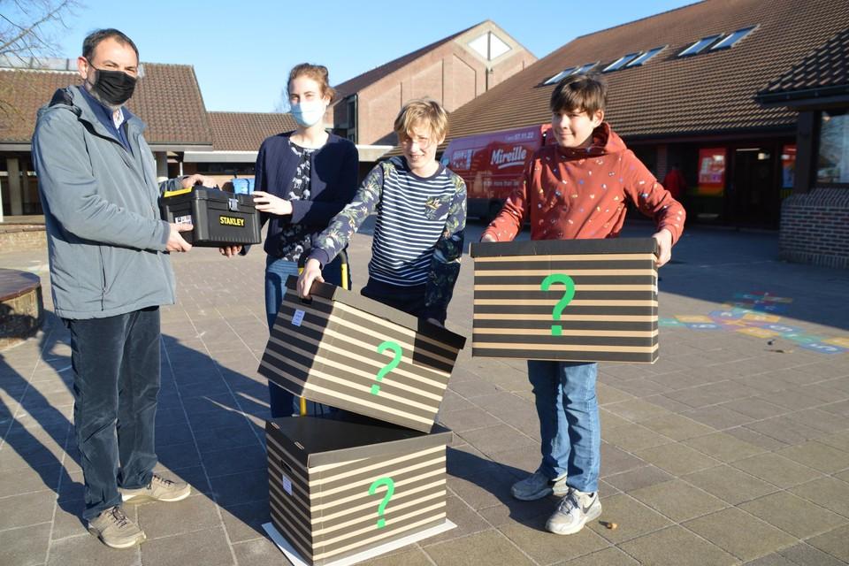 Staf Teunen overhandigt een bak met gereedschap aan juf Ine van de school Beuk & Noot. Hiermee kunnen Vic (11) en Bram (11) samen met de rest van de zesdeklassers de verrassingspakketten die in de technoboxen zitten in elkaar knutselen.