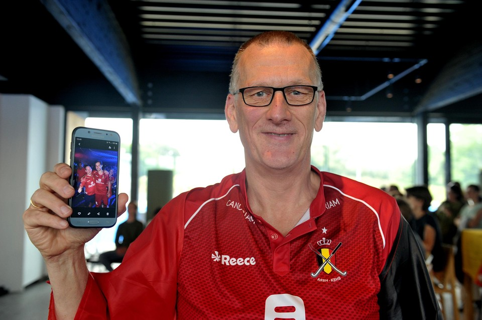 """Joost Vandepontseele, de fanatiekste supporter van heel de zaal, toont een foto van een van de Red Lions met zijn zoon. """"Ik ken veel van die spelers goed. Zo'n betrokkenheid heb ik nog nooit gevoeld."""""""