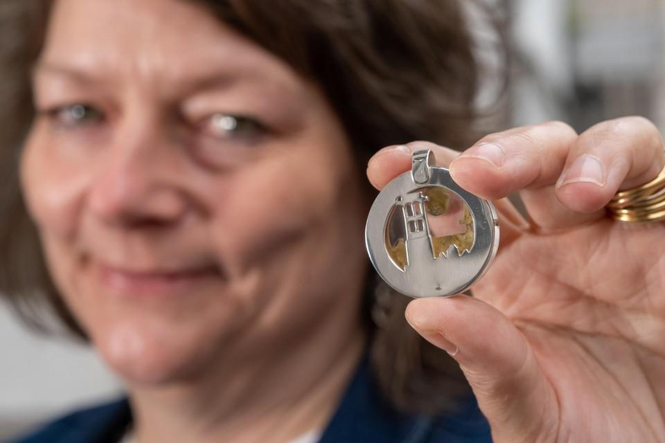 Goudsmid Annick Igo toont een van haar sleutelhangers van de Sint-Romboutstoren.
