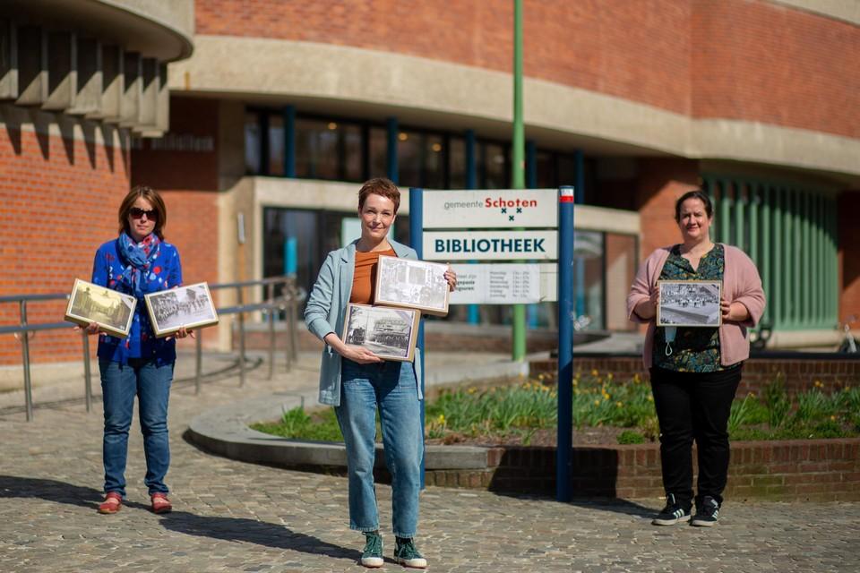 Schepen Iefke Hendrickx en Charlotte Klima tonen de erfgoedpuzzels samen met bibliothecaris Liesbeth Van Camp.