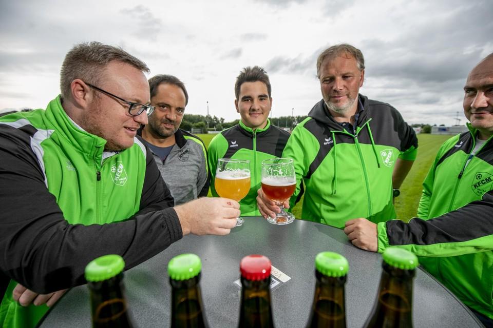 De bestuursleden heffen het glas op en met hun nieuwe biertjes.