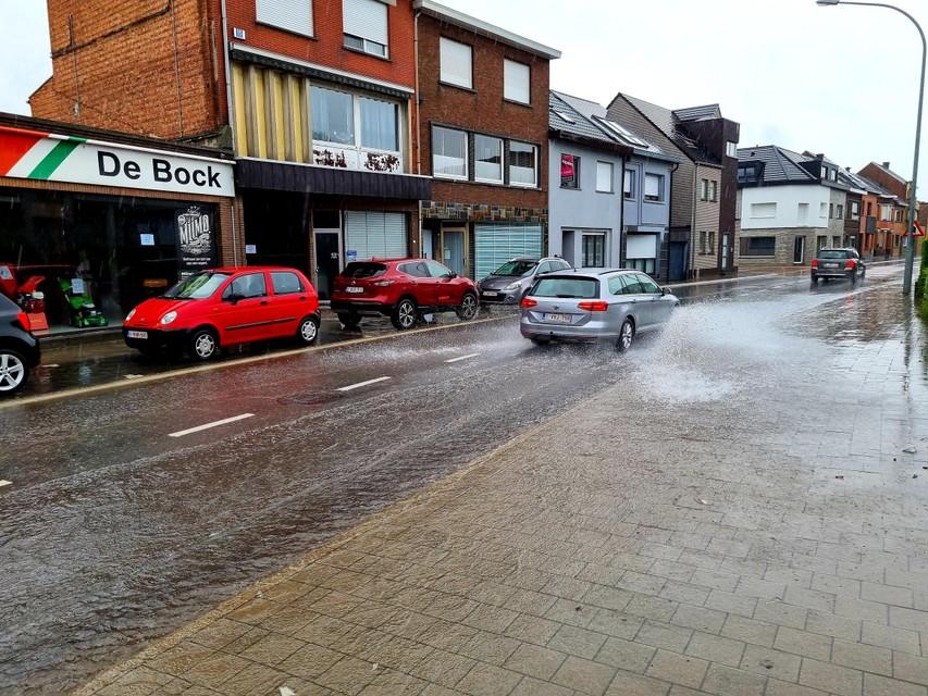 De auto's bleven door de ondergelopen straat rijden, waardoor het water flink opspatte.