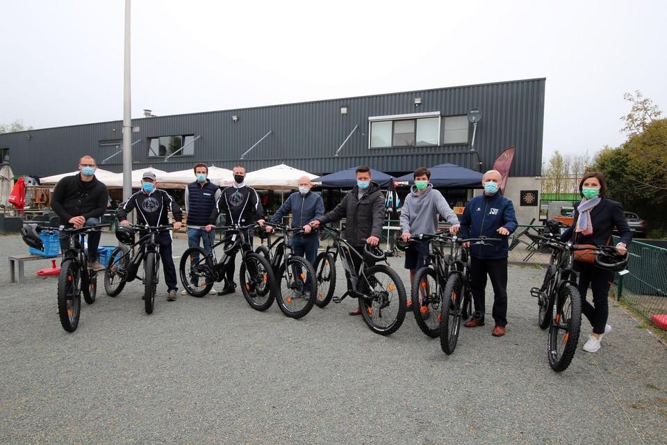 Johnny, tweede van links, en Tim Janssens, vierde van links, stellen hun elektrische mountainbikes voor.