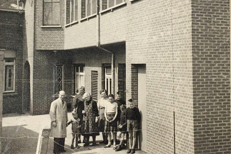 Karel Van Peer en zijn familie staan enkele tientallen jaren geleden bij het naaiatelier van de kledingzaak in Poederlee.