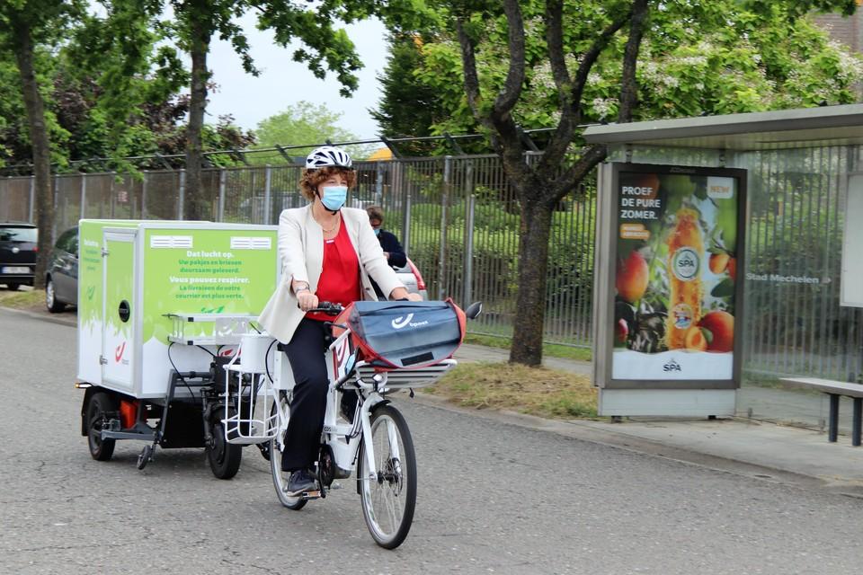 Minister Petra De Sutter test zelf een elektrische fiets met trailer uit.