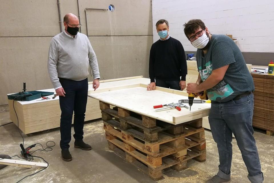 Dirk Mertens van Kaliber (links) en Luc Peetermans van De Bedstee (midden) kijken toe hoe medewerker Ragnan van maatwerkbedrijf Kaliber aan een houten onderdeel van Unieco werkt.