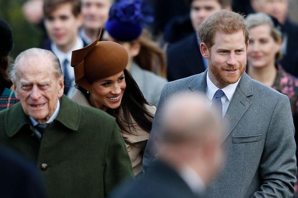 Prins Harry (rechts) zal zaterdag aanwezig zijn op de begrafenis van prins Philip (links), zijn echtgenote Meghan Markle (centraal) blijft op doktersadvies in Californië.