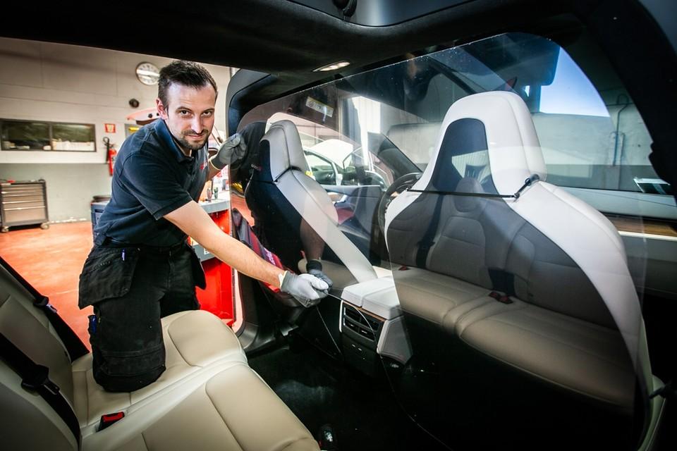 Dimas Van Rompaey toont hoe hij een plexiplaat in een taxi installeert.
