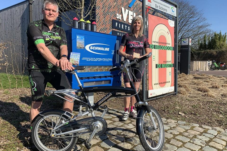 Peter Van Den Abbeele en Carina Cortebeeck van de Schorretrappers met de 'In-A-Box'-fietsroute aan de automaat aan fietsknooppunt 26 en de te winnen fiets met de fietszoektocht.