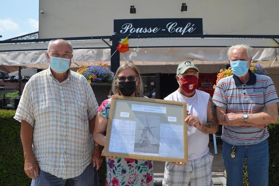 Sonja De Wolf van Pousse-Café met de ingelijste stichtingsakte van de Molekenskermis, te midden van haar klanten Neel, Frank en Johannes.