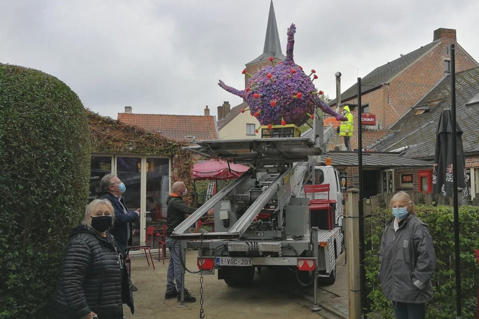 Agnes Janssens (links) en Jenny Verelst (rechts) kijken toe hoe het coronavirus naar het dak van café Welkom in Noorderwijk wordt geleid.