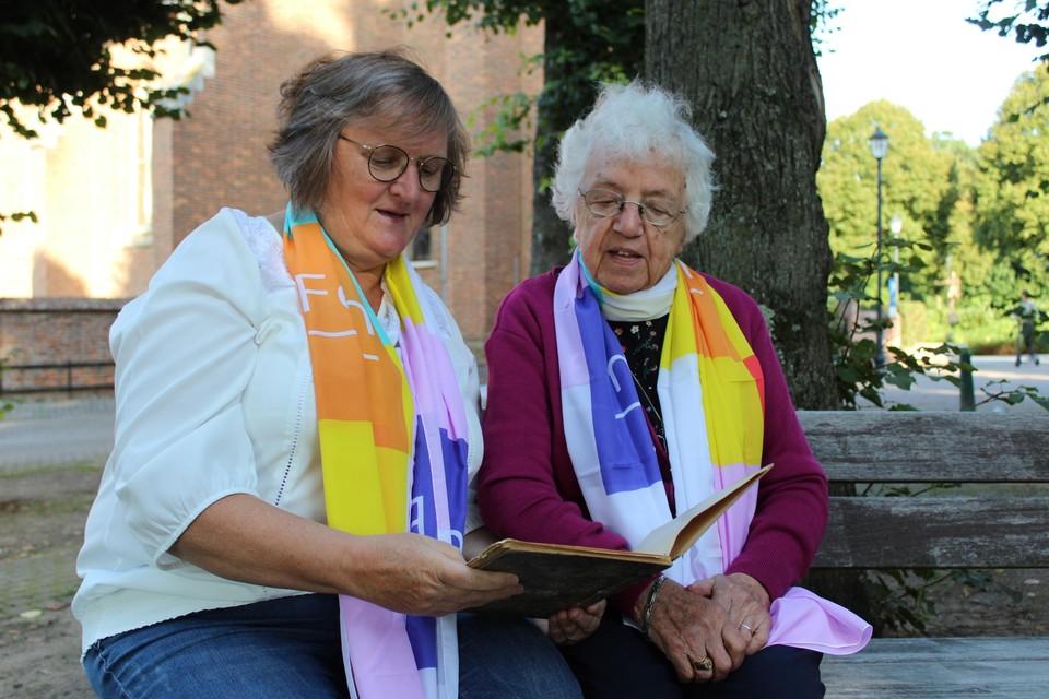 Lea Goos en Mia Tessens bekijken het oude verslagboek