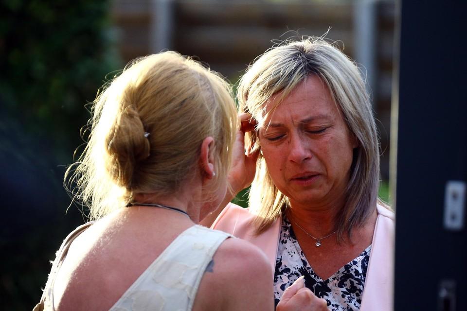De vriendin van Conings wordt getroost door een familielid.