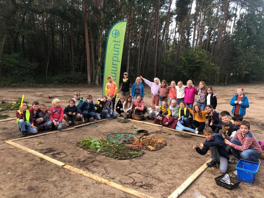 De leerlingen van het vijfde leerjaar van 't Klavernest staan bij het natuurschilderij dat de meisjes hebben gemaakt in de Visbeekvallei in Wechelderzande.