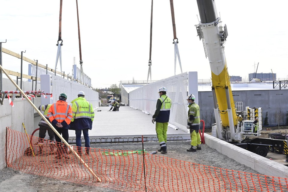 De metalen fietsersbrug werd vrijdag op haar plaats naast de nieuwe brug over de R6 gehesen.