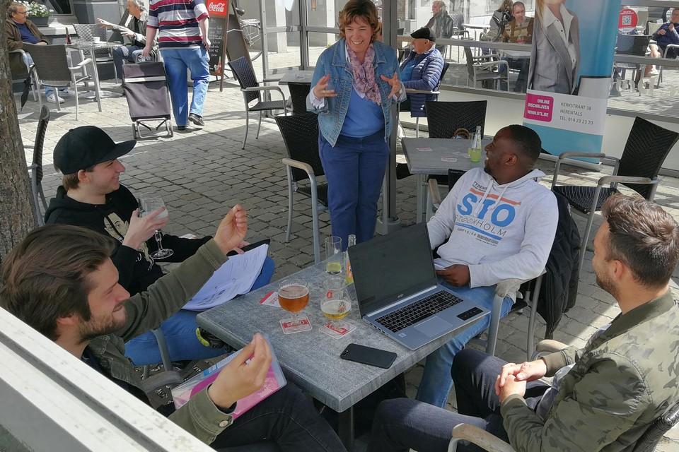 Studenten Seppe Stroobants, Jef Brabants, Wietse Bosmans en Solomon Mawumawu krijgen op het terras van café Druyts les van informaticaleerkracht Marijke Vandoninck.