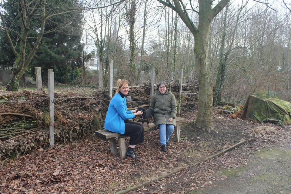 Directeur Doreen Rogiers (links) in de tuin van buurvrouw Betty Minnebo (rechts). Achter hen ligt het bosje dat de leerlingen in de toekomst mogen gebruiken.