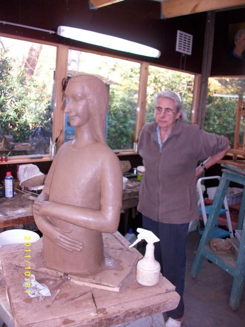Mariëtte Coppens in haar atelier, boetserend aan het beeld van Anne Frank.