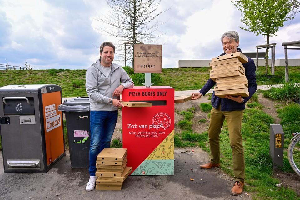 Jan Van Leuffel van City Ants Agents en Bernard Sironval van pizzarestaurant Otomat introduceren de pizzadozenvuilbak aan de Scheldekaaien.