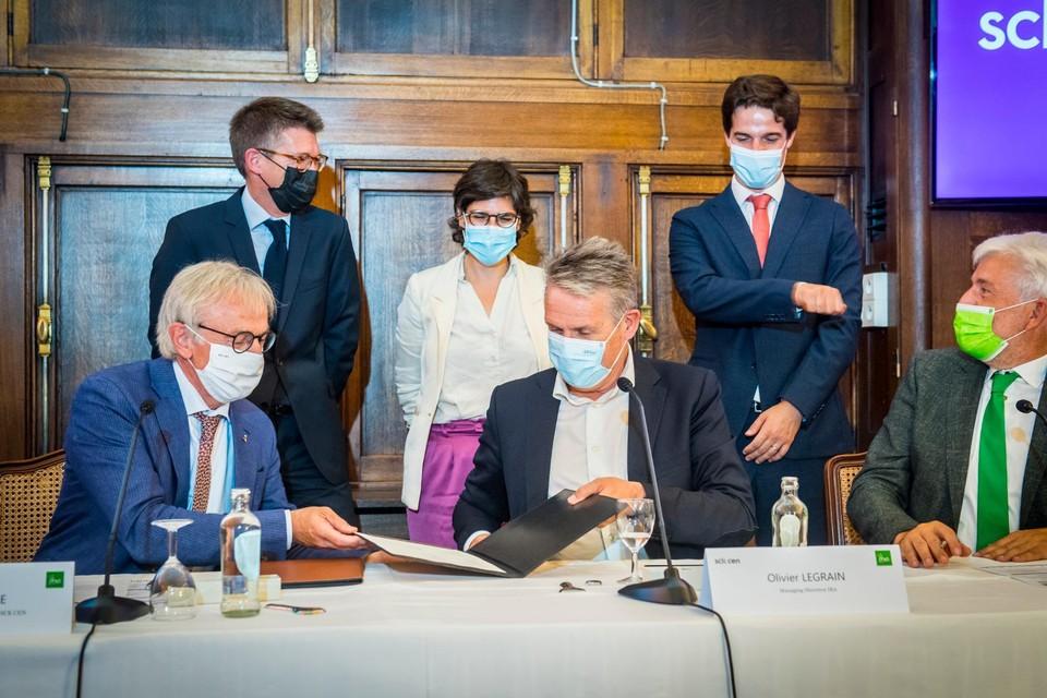 Eric van Walle, directeur-generaal van het SCK en Olivier Legrain, CEO van IBA, ondertekenen in aanwezigheid van onder meer vice-eersteminister Pierre-Yves Dermagne en Energieminister TinneVan Der Straeten het samenwerkingsakkoord.