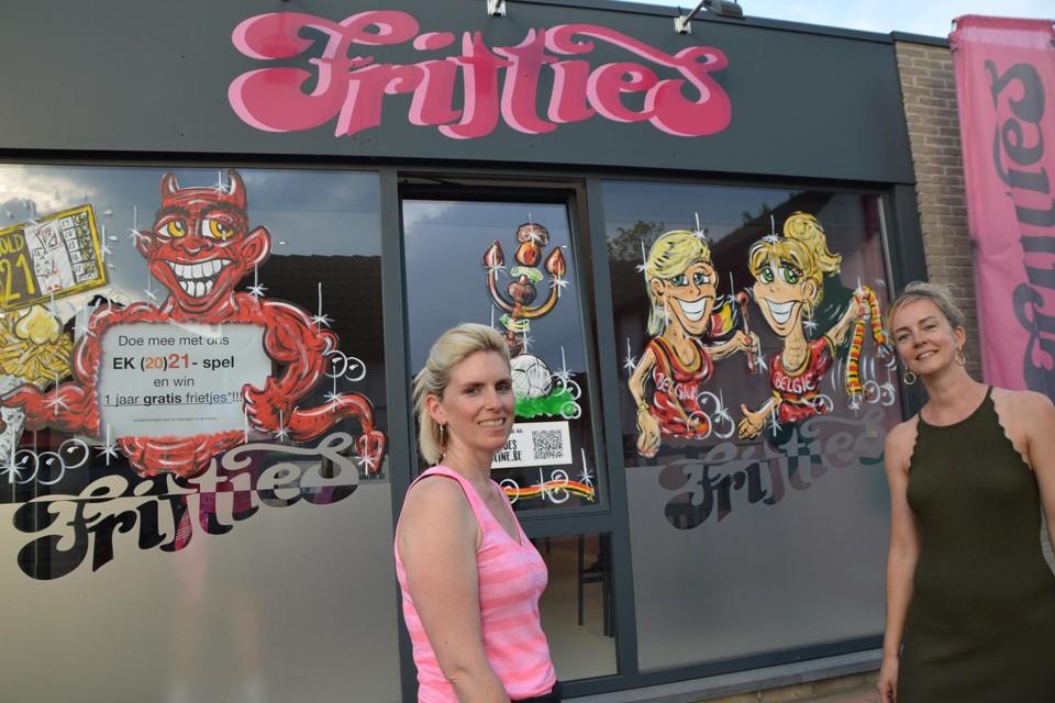 Nancy De Rademaeker en Heidi Desnyder voor hun frituur Fritties met rechts hun karikaturen.
