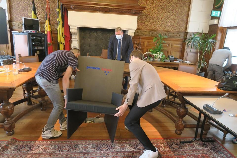 Sam en Abdul dragen de stoel van de burgemeester naar binnen.