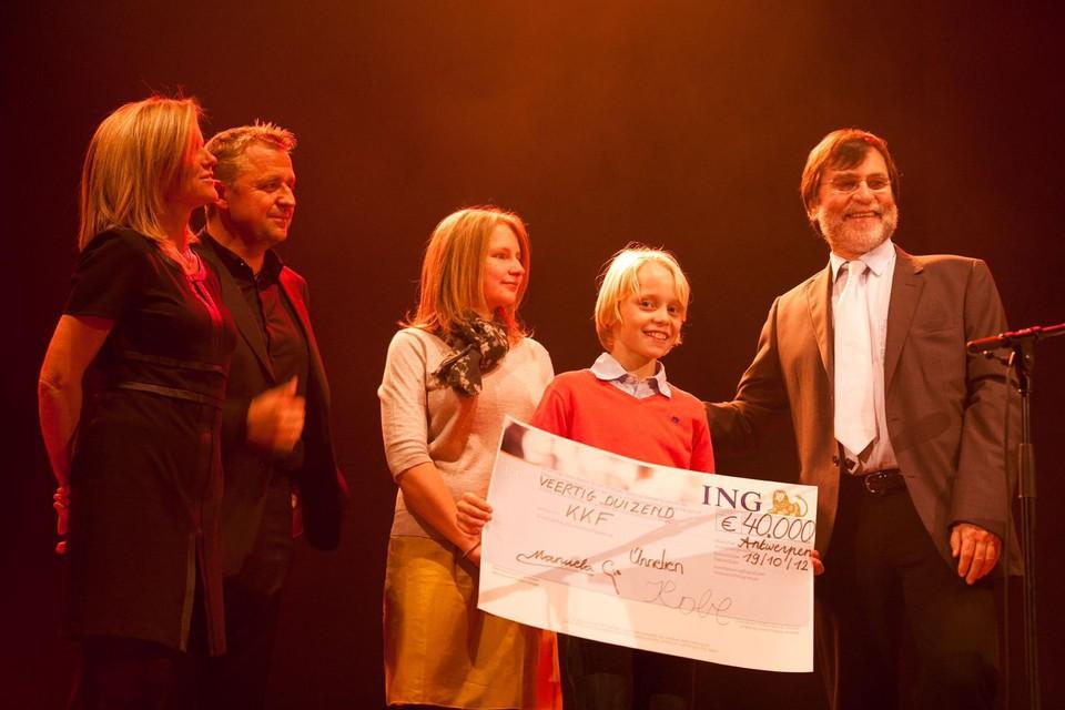 Manuela en Gie samen met hun twee andere kinderen Annelien en Kobe op het podium van de voorlopig laatste Muziek voor Sander in 2012 met een flinke cheque voor prof. dr. Yves Benoit van het UZ Gent en Kinderkankerfonds.