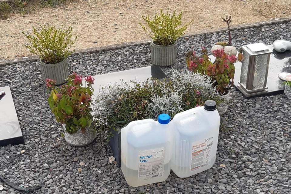 Enkele bidons met water en onderhoudsproduct bij een graf.