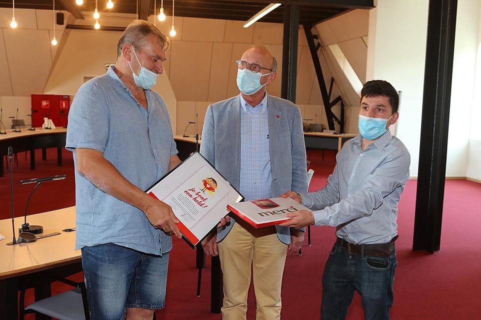 Rudy Gevaert krijgt van burgemeester Boogaerts de oorkonde en van vader Saleq Nazavy een doos bonbons.