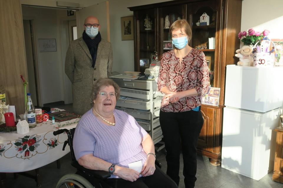 Operatie vaccinatie geslaagd. Tineke Szyr werd beschermd door haar kleindochter en coördinerend arts Anneleen Vanneuville. Burgemeester Dirk Bauwens kwam de operatie van nabij volgen.