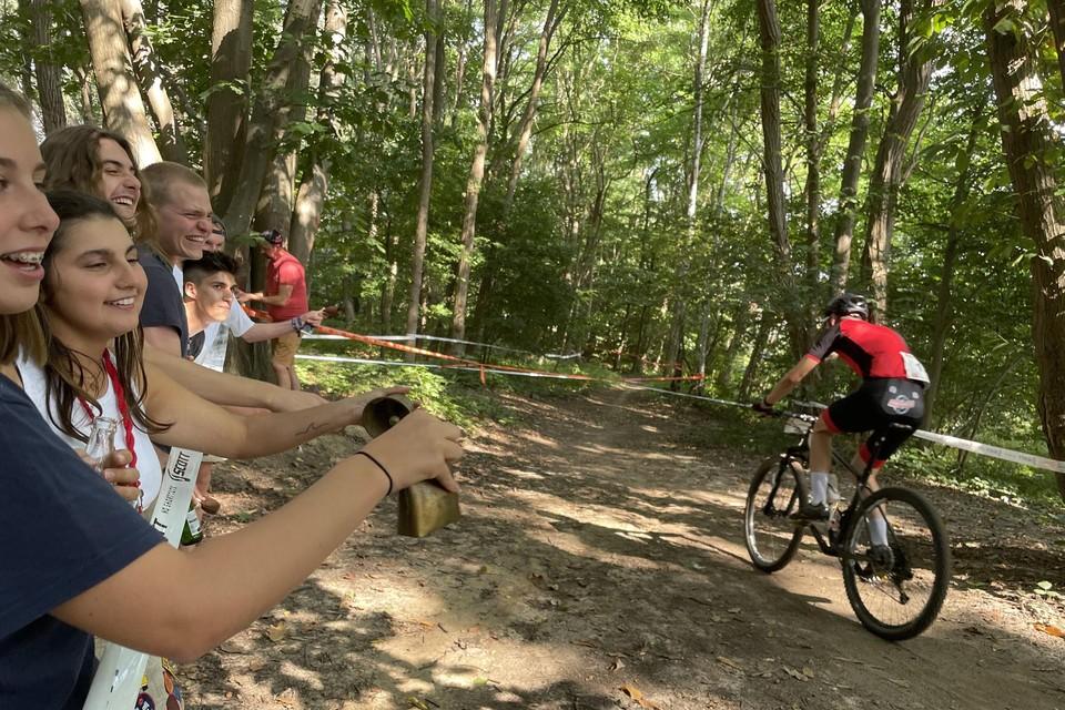 De meisjes en jongens van Chiro Heist-centrum moedigen de renners in het Bergbos aan met een Zwitserse vlag en koebellen.