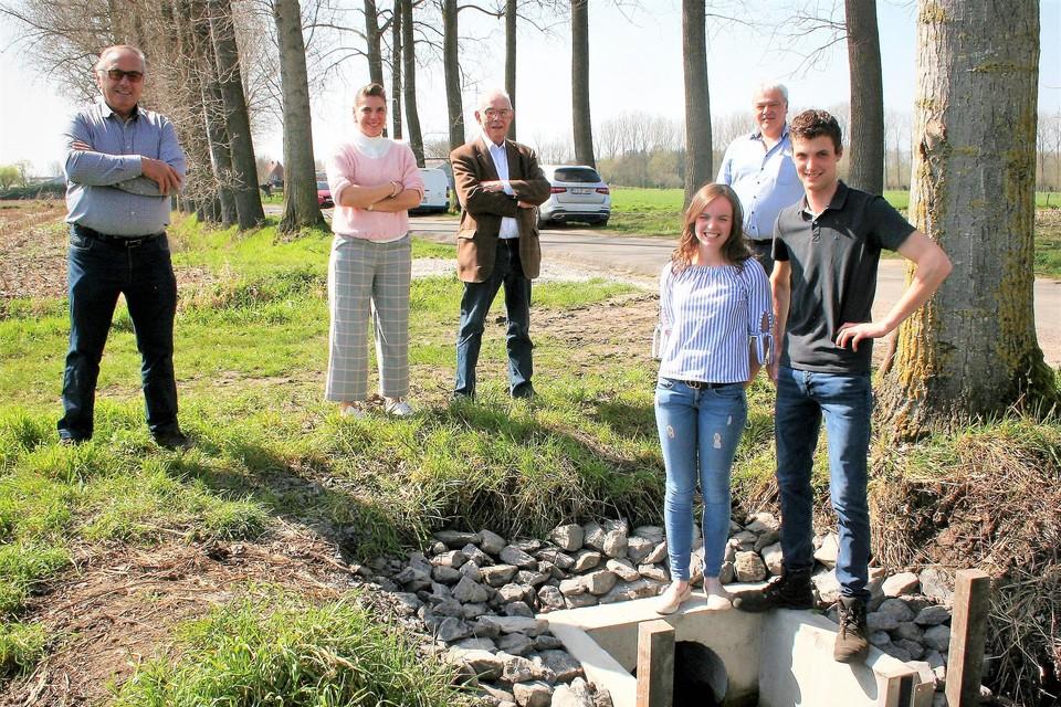 Bedenker Jonas Dhollander samen met zijn vriendin en een delegatie van het polderbestuur Sinaai-Daknam bij de microsluis aan de Heirstraat.