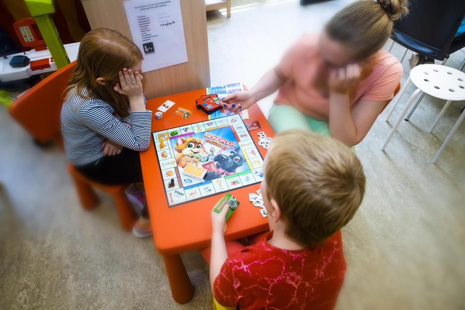 Een begeleidster speelt Monopoly met twee kinderen.