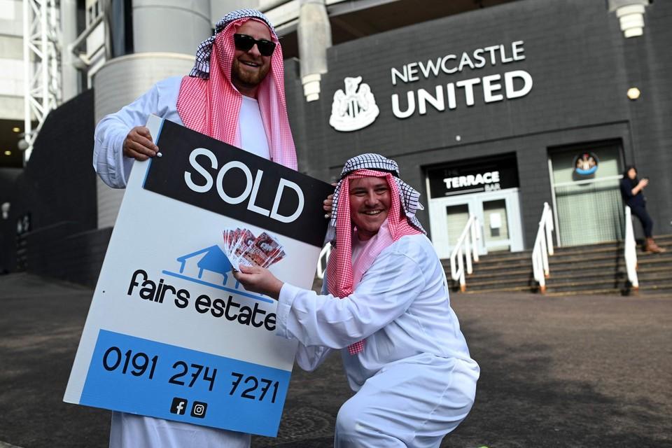 Verklede fans van Newcastle poseren voor de ingang van St. James' Park, het stadion van de Engelse eersteklasser.