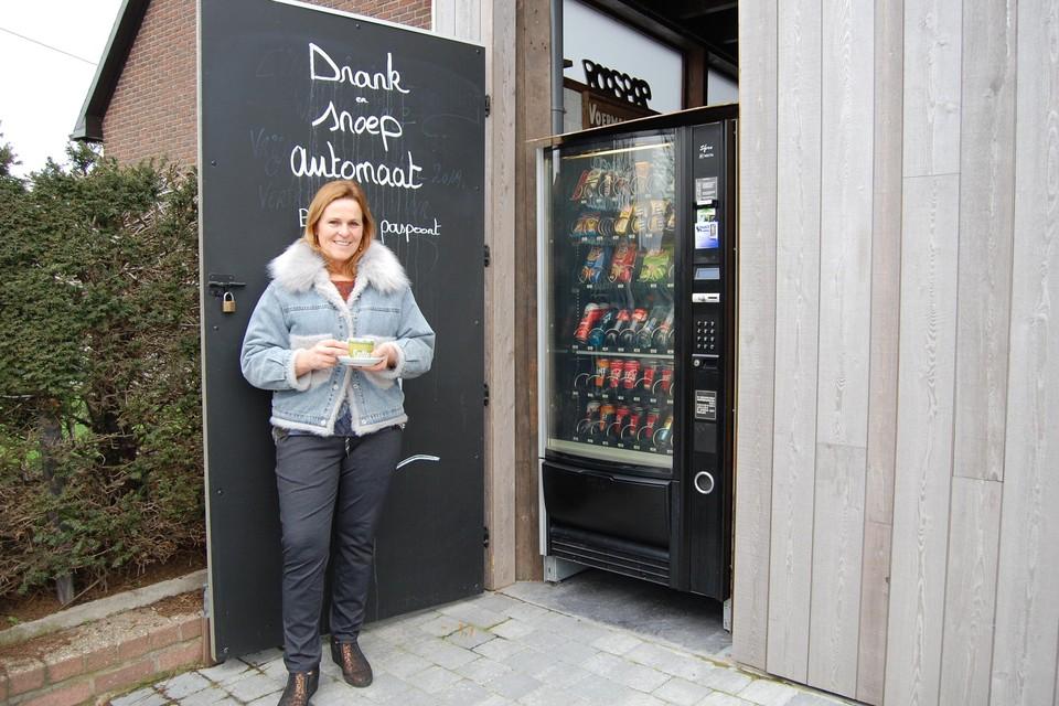 Marleen van café De Voermansrust bij haar gloednieuwe drank- en snoepautomaat.