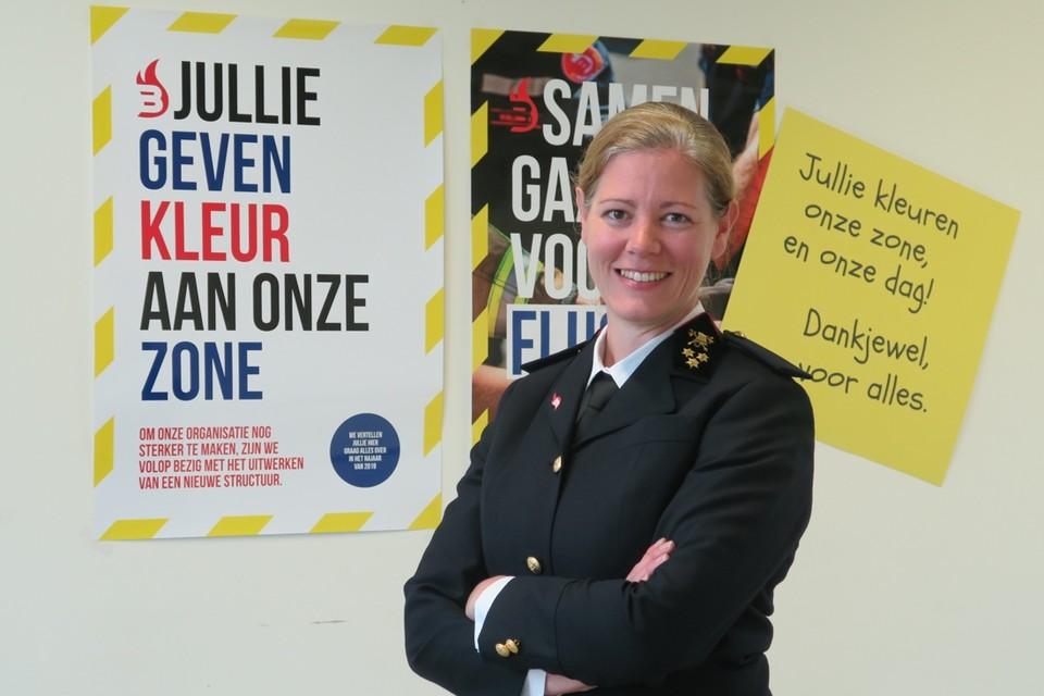 Katrien De Maeyer in haar chicste uniform van zonecommandant. De drie sterren op de manchetten zijn een verwijzing naar haar graad van kapitein. Op de achtergrond hangen de affiches die het nieuwe beleidsplan met faciliteren, leren, uitdagen en ontmoeten (Fluo) als kernbegrippen.