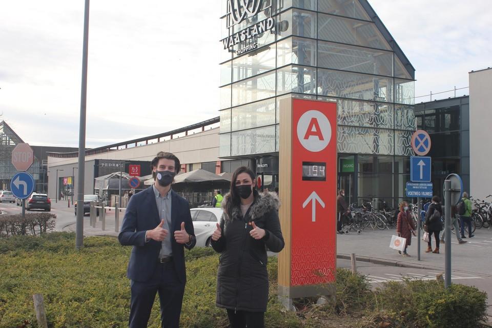 Vincent Hermans en Lesley-Anne Smet aan een digitaal paneel op de parking. Zo kan u ook zonder smartphone zien hoeveel vrije plaatsen er nog zijn.